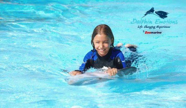 Criança a nadar com os golfinhos.