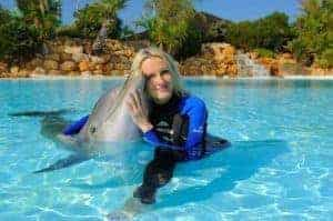 Guest enjoying a cuddle with one of the Zoomarine dolphins