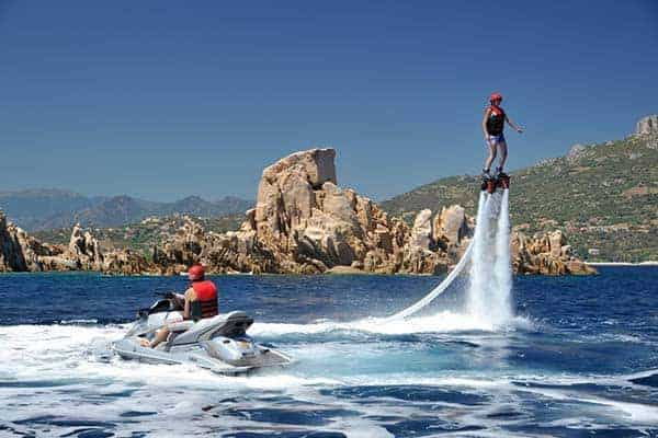 Men doing flyboarding and another on a jet ski