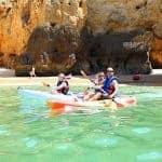 Kayaks paddle close to a pretty beach