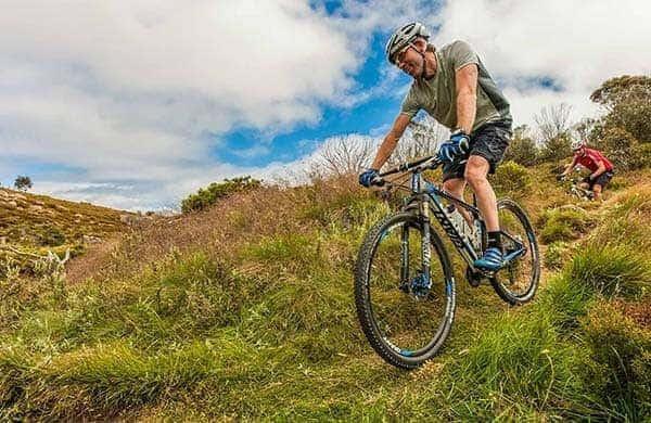 dos ciclistas bajando por la montaña - Sagres