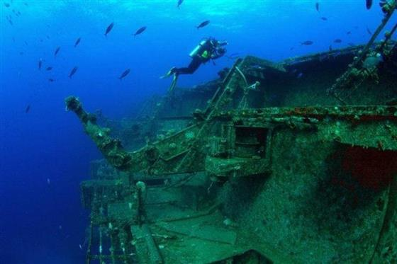 Men Scuba Diving near thinked ship