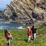 3 people walking by the sea and cliff on the west coast