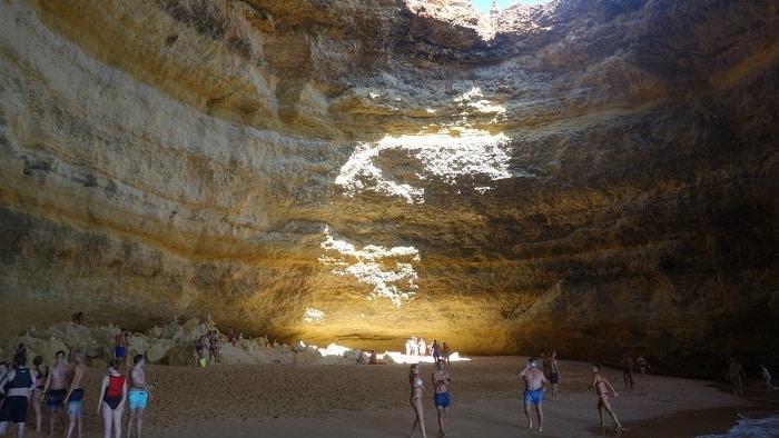 interior da gruta de Benagil com luz a entrar de cima e pessoas na praia