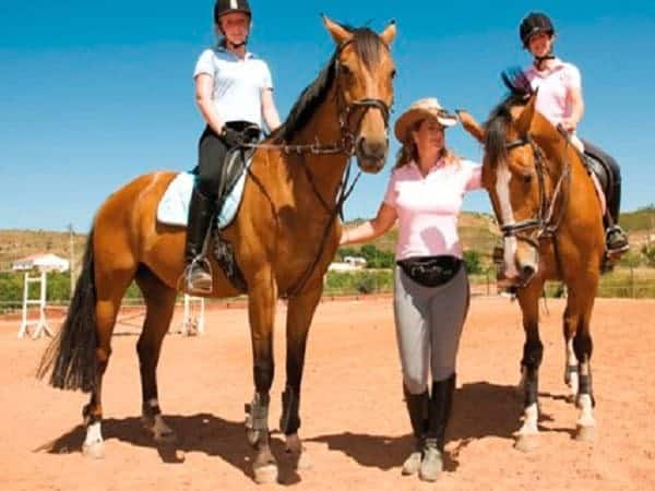 Two girls and an instructor with horses