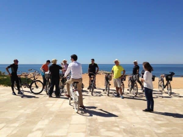 Grupo de bicicleta, com o mar ao fundo.
