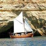 Sailing boat leãozinho in front of rock formations, with cave entrance.