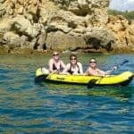 Three ladies on a yellow kayak near some rock formations.