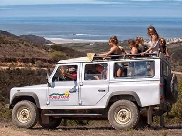 Group in a jeep, on a dirt road with a beach in the back.
