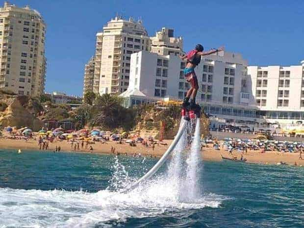 Person on the flyboard with the beach and buildings in the background, Armação de Pêra.
