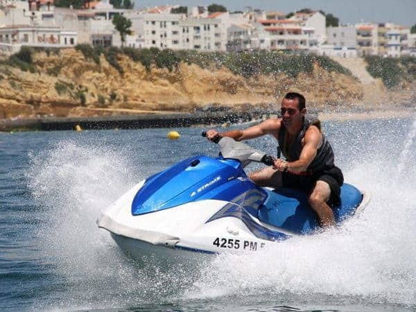Man on a jet ski, with brach and buildings on the background, Albufeira.