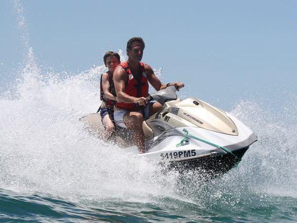 padre con su hijo en una moto de agua