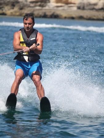 Man doing water ski, on the left Armação de Pêra.