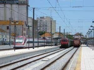 Ligne de trains - à gauche, un train Alfa Pendular qui attend de rentrer à Porto, au centre, un train interurbain qui ira jusqu'à Lisbonne et à droite, le train de passage.
