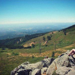 mulher sentada nos rochedos em Fóia, Monchique observandoa vista