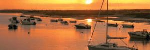 Cabanes de Tavira au coucher du soleil avec quelques bateaux