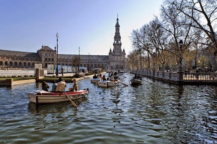 Praça de Espanha em Sevilha e pessoas em pequenos barcos a passear no rio