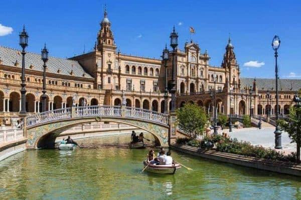 Catedral de Sevilha com rio à frente e barcos a remos a passar debaixo da ponte