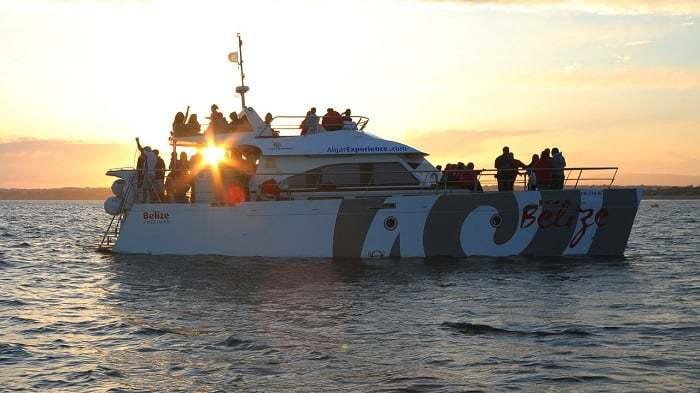 pasajeros disfrutando de la puesta de sol desde un catamarán