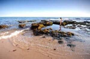 criança a brincar nas piscinas da Praia de Vale de Centeanes.