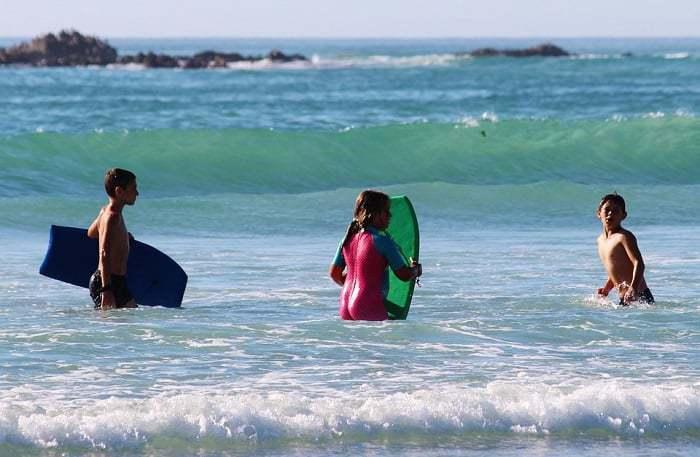 niños en el agua con tablas de bodyboard