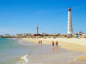 playa de Faro con turistas paseando por la orilla y el Faro de fondo