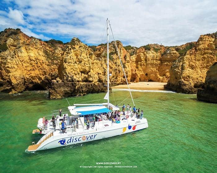 Catamarán Discover con pasajeros observando la costa de Lagos