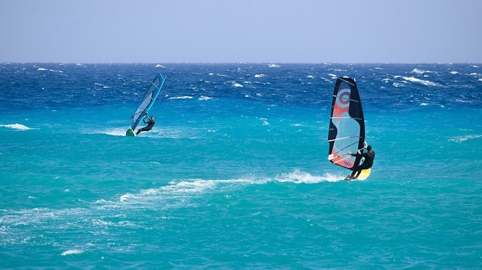 e men Windsurfing with beutiful bue sea in the Algarve
