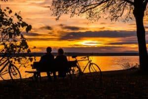 silueta de pareja sentada en un banco con una bici y el atardecer de fondo
