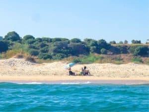 dos personas tomando el sol en la orilla de praia da Terra Estreita