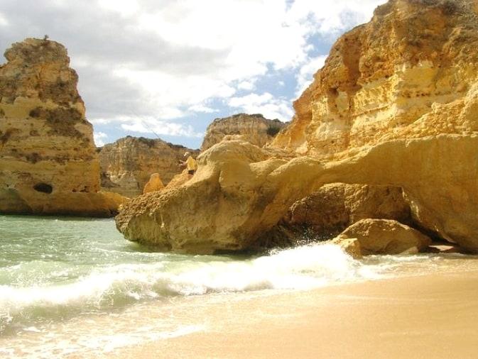 praia de Vale De Centeanes con la ola rompiendo en la orilla y formaciones rocosas típicas